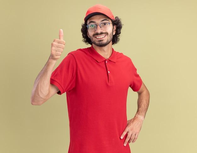 Glimlachende jonge bezorger in rood uniform en pet met bril kijkend naar voorkant, hand op taille houdend met duim omhoog geïsoleerd op olijfgroene muur met kopieerruimte