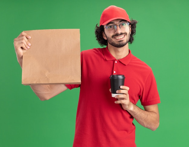 Glimlachende jonge bezorger in rood uniform en pet met bril met papieren pakket en plastic koffiekopje kijkend naar voorkant geïsoleerd op groene muur