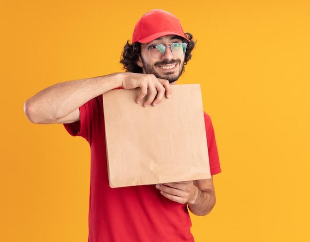 Glimlachende jonge bezorger in rood uniform en pet met bril met papieren pakket kijkend naar voorkant geïsoleerd op oranje muur met kopieerruimte