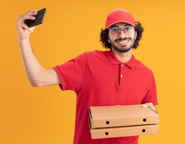 Glimlachende jonge bezorger in rood uniform en pet met een bril die pizzapakketten vasthoudt en naar de voorkant kijkt en selfie neemt geïsoleerd op een oranje muur