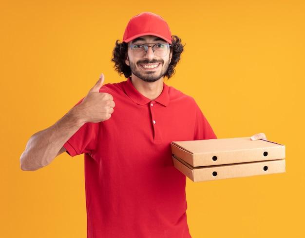 Glimlachende jonge bezorger in rood uniform en pet met een bril die pizzapakketten vasthoudt en naar de voorkant kijkt met duim omhoog geïsoleerd op een oranje muur