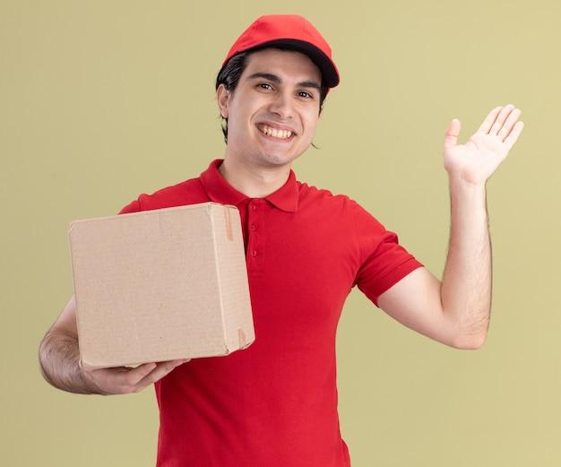 Glimlachende jonge bezorger in rood uniform en pet met kartonnen doos kijkend naar de voorkant met lege hand geïsoleerd op olijfgroene muur