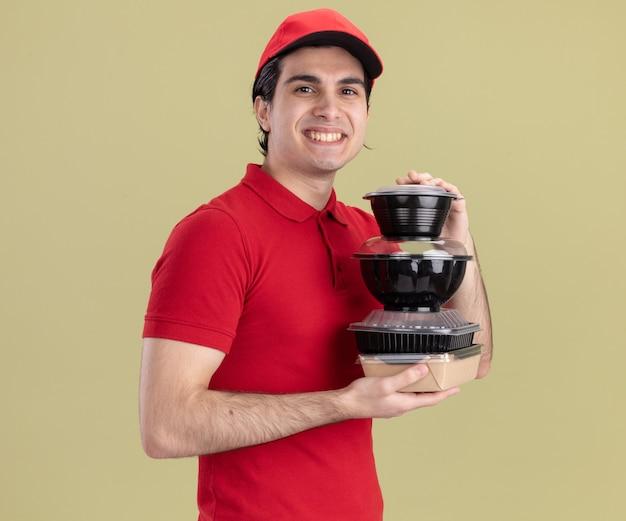 Glimlachende jonge bezorger in rood uniform en pet staande in profielweergave met voedselcontainers en papieren voedselpakket kijkend naar voorkant geïsoleerd op olijfgroene muur