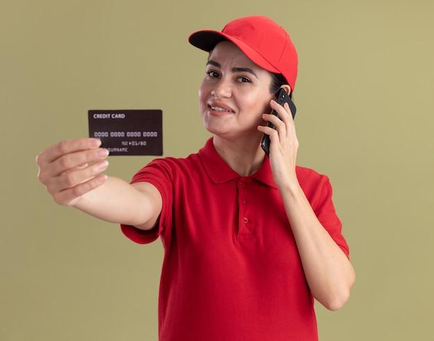 Glimlachende jonge bezorger in uniform en pet die creditcard naar voren uitstrekt en aan de telefoon praat en naar de voorkant kijkt geïsoleerd op olijfgroene muur