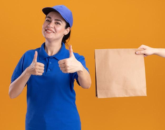 Glimlachende jonge bezorger in uniform en pet met duimen omhoog en iemand die een papieren pakket naar haar uitrekt, geïsoleerd op een oranje muur