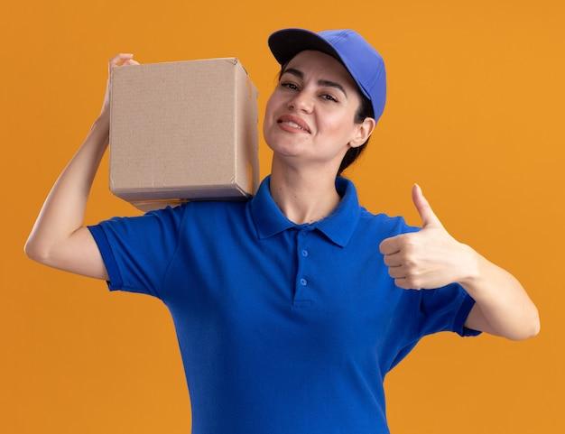 Glimlachende jonge bezorger in uniform en pet met kartonnen doos op schouder met duim omhoog geïsoleerd op oranje muur
