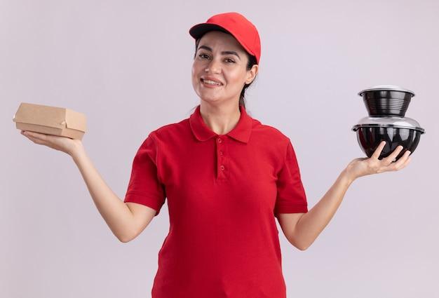 Glimlachende jonge bezorger in uniform en pet met papieren voedselpakket en voedselcontainers kijkend naar de voorkant geïsoleerd op een witte muur