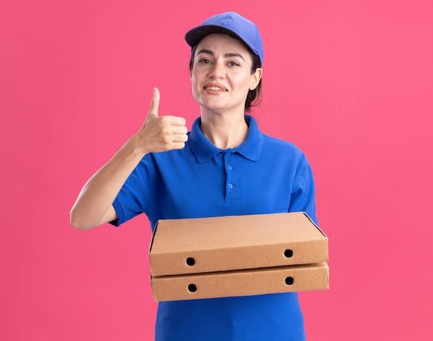 Glimlachende jonge bezorger in uniform en pet met pizzapakketten met duim omhoog geïsoleerd op roze muur