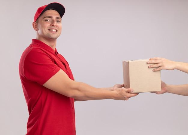 Glimlachende jonge bezorger in uniform met dop die doos geeft aan klant geïsoleerd op een witte muur