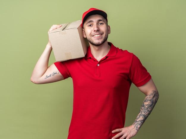 Glimlachende jonge bezorger in uniform met dop met doos op schouder
