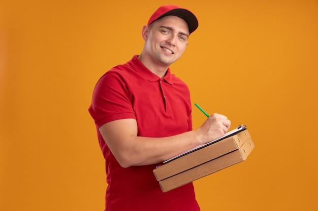 Glimlachende jonge bezorger in uniform met pet die pizzadozen vasthoudt en iets schrijft op klembord geïsoleerd op een oranje muur