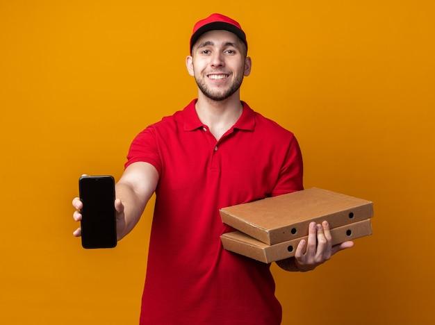 Glimlachende jonge bezorger in uniform met pet die pizzadozen vasthoudt en telefoon laat zien
