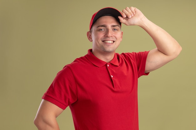 Glimlachende jonge bezorger met uniform en pet met pet geïsoleerd op olijfgroene muur