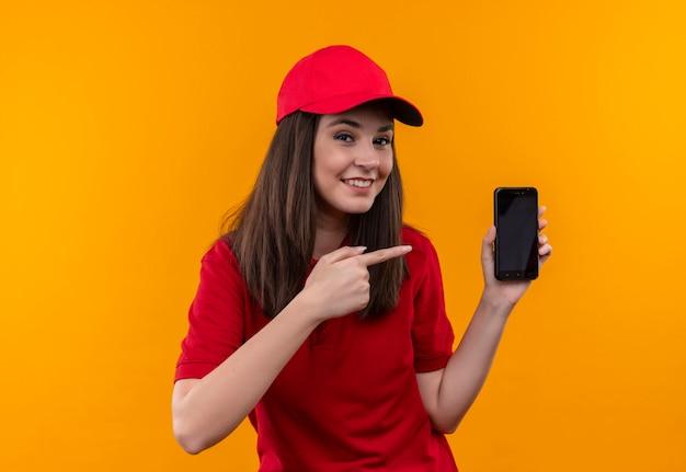 Glimlachende jonge bezorgvrouw die een rood t-shirt in een rode pet draagt en met de ene hand de telefoon vasthoudt en ernaar wijst met de andere hand op de geïsoleerde gele muur