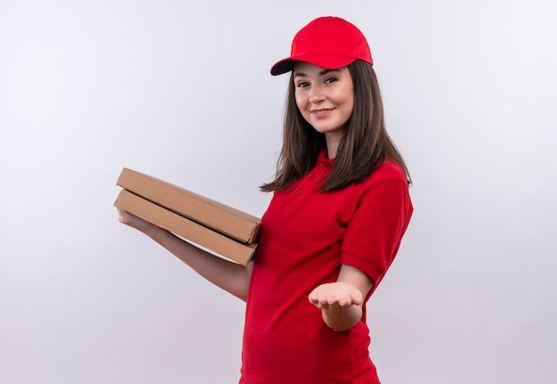 Glimlachende jonge bezorgvrouw die rode t-shirt in rode pet draagt die een pizzadoos houdt en haar hand op geïsoleerde witte muur steekt