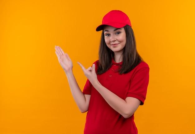 Glimlachende jonge bezorgvrouw die rode t-shirt in rode pet draagt en hand en vinger naar de zijkant op geïsoleerde oranje muur wijst