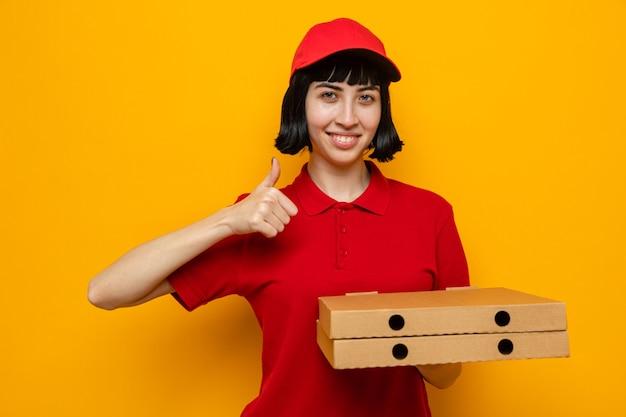 Glimlachende jonge blanke bezorger die pizzadozen vasthoudt en omhoog steekt