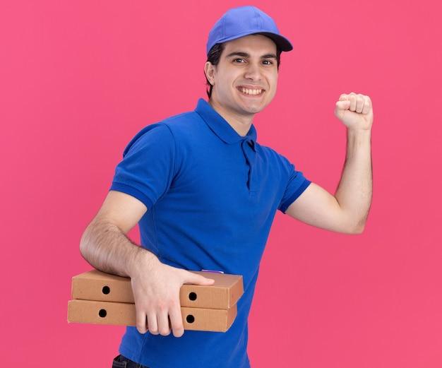 Glimlachende jonge blanke bezorger in blauw uniform en pet die in profielweergave staat en pizzapakketten vasthoudt die een kloppend gebaar doen geïsoleerd op roze muur