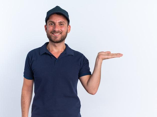 Glimlachende jonge blanke bezorger in blauw uniform en pet kijkend naar camera met lege hand geïsoleerd op een witte muur
