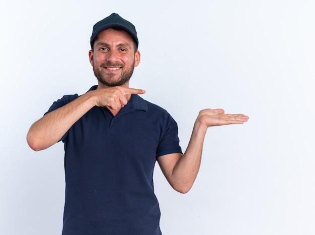 Glimlachende jonge blanke bezorger in blauw uniform en pet kijkend naar camera met lege hand wijzend naar kant geïsoleerd op witte muur
