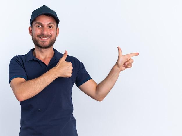Glimlachende jonge blanke bezorger in blauw uniform en pet met duim omhoog wijzend naar de zijkant