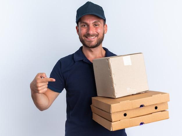 Glimlachende jonge blanke bezorger in blauw uniform en pet met pizzapakketten en kartonnen doos wijzend naar hen kijkend naar camera geïsoleerd op een witte muur