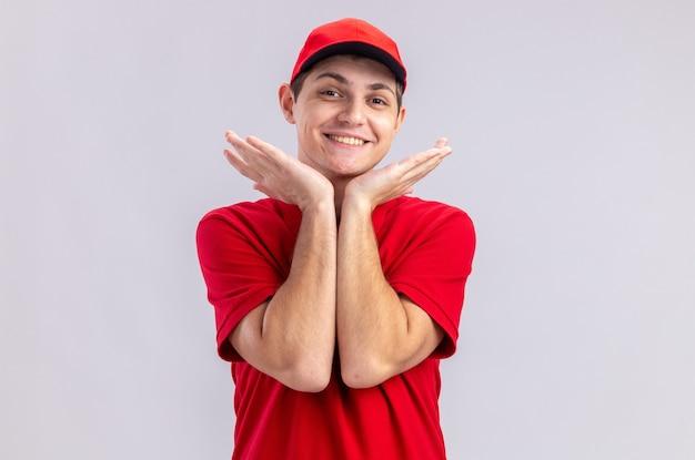 Glimlachende jonge blanke bezorger in rood shirt houdt handen dicht bij zijn gezicht