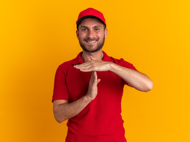 Glimlachende jonge blanke bezorger in rood uniform en pet die een time-outgebaar doet