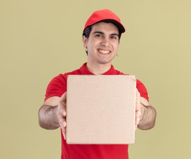 Glimlachende jonge blanke bezorger in rood uniform en pet die kartonnen doos uitrekt