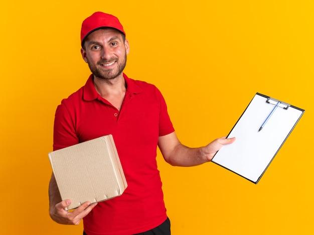 Glimlachende jonge blanke bezorger in rood uniform en pet kijkend naar camera met kartonnen doos met klembord geïsoleerd op oranje muur