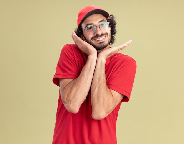 Glimlachende jonge blanke bezorger in rood uniform en pet met bril die handen in de buurt van gezicht houdt geïsoleerd op olijfgroene muur met kopieerruimte