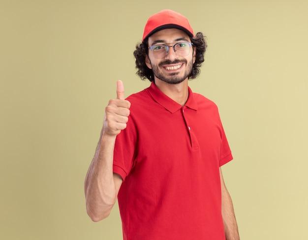 Glimlachende jonge blanke bezorger in rood uniform en pet met een bril die duim omhoog laat zien geïsoleerd op olijfgroene muur met kopieerruimte