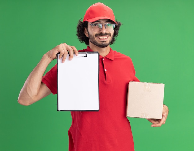 Glimlachende jonge blanke bezorger in rood uniform en pet met een bril die een kartonnen doos vasthoudt en een klembord toont