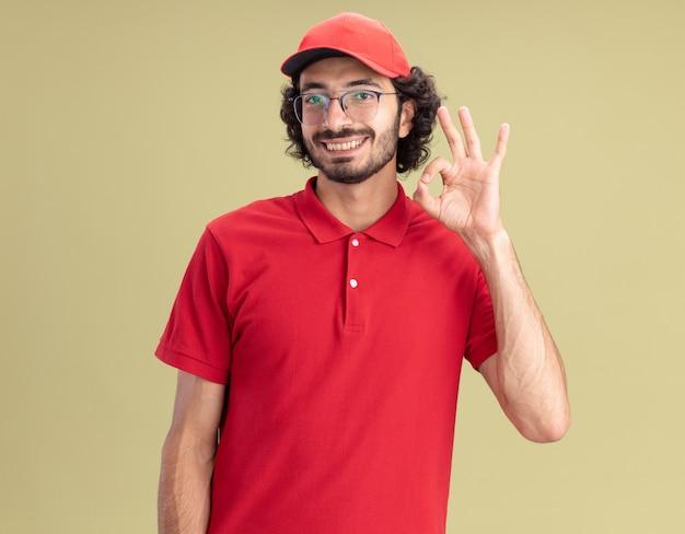 Glimlachende jonge blanke bezorger in rood uniform en pet met een bril die een ok teken doet dat op een olijfgroene muur wordt geïsoleerd