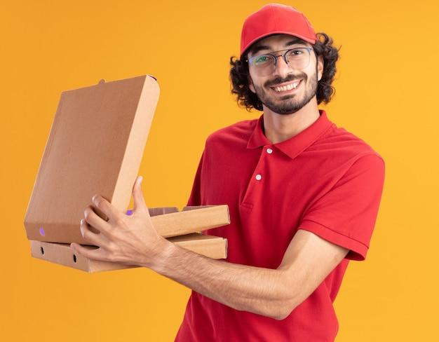 Glimlachende jonge blanke bezorger in rood uniform en pet met een bril die pizzapakketten vasthoudt die er een openen