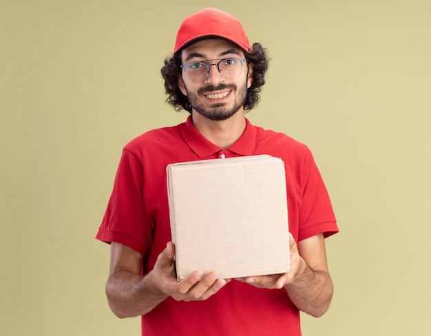 Glimlachende jonge blanke bezorger in rood uniform en pet met een bril met kartonnen doos