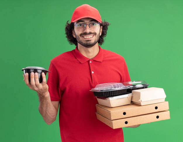 Glimlachende jonge blanke bezorger in rood uniform en pet met een bril met pizzapakketten met papieren voedselpakketten en voedselcontainers erop