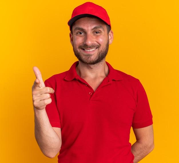Glimlachende jonge blanke bezorger in rood uniform en pet met hand achter de rug kijkend en wijzend naar camera geïsoleerd op oranje muur