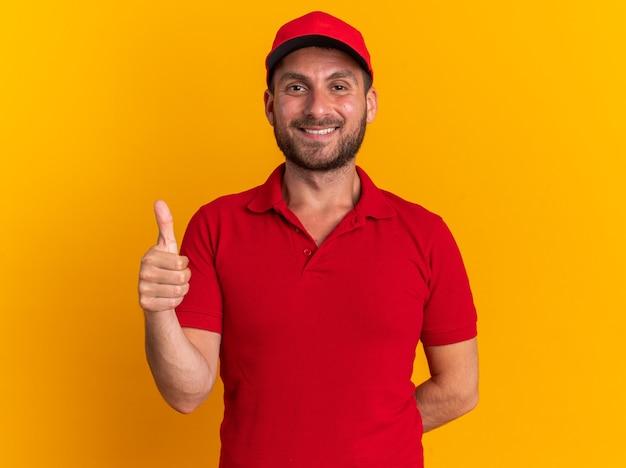 Glimlachende jonge blanke bezorger in rood uniform en pet met hand achter de rug kijkend naar camera met duim omhoog geïsoleerd op oranje muur