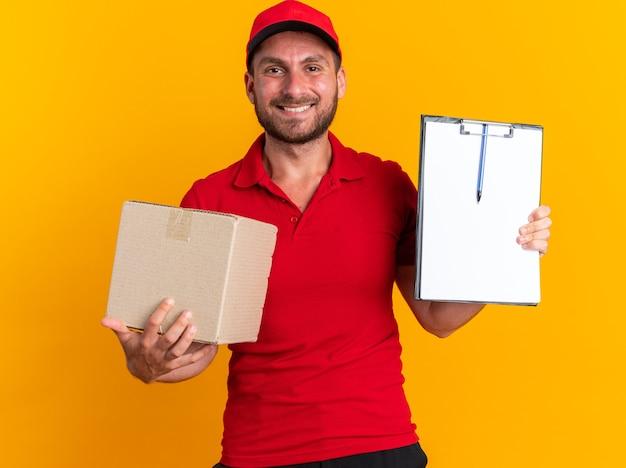 Glimlachende jonge blanke bezorger in rood uniform en pet met kartonnen doos met klembord