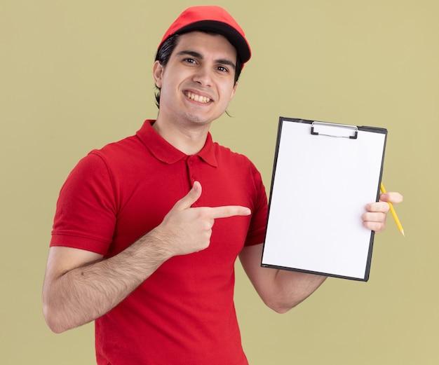 Glimlachende jonge blanke bezorger in rood uniform en pet met klembord naar camera wijzend met potlood in de hand