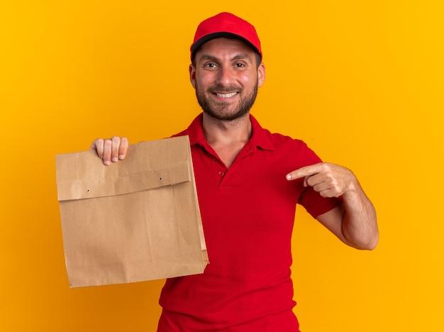 Glimlachende jonge blanke bezorger in rood uniform en pet met papieren pakket wijzend erop kijkend naar camera geïsoleerd op oranje muur