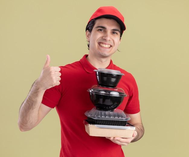 Glimlachende jonge blanke bezorger in rood uniform en pet met voedselcontainers en papieren voedselpakket met duim omhoog geïsoleerd op olijfgroene muur