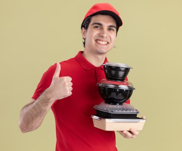 Glimlachende jonge blanke bezorger in rood uniform en pet met voedselcontainers en papieren voedselpakket met duim omhoog