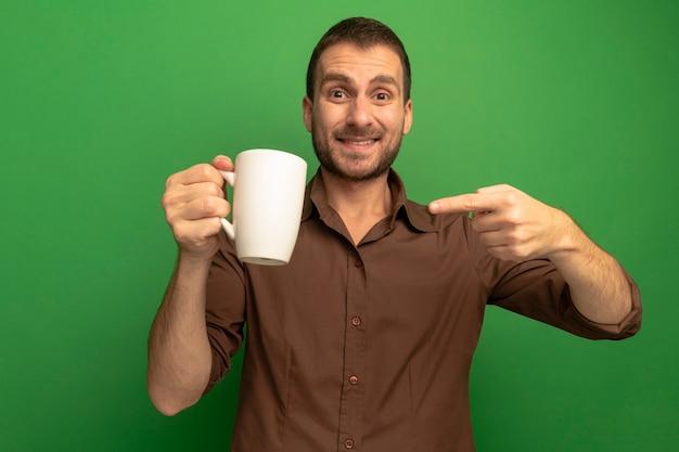 Glimlachende jonge blanke man houden en wijzend op kopje thee kijken camera geïsoleerd op groene achtergrond
