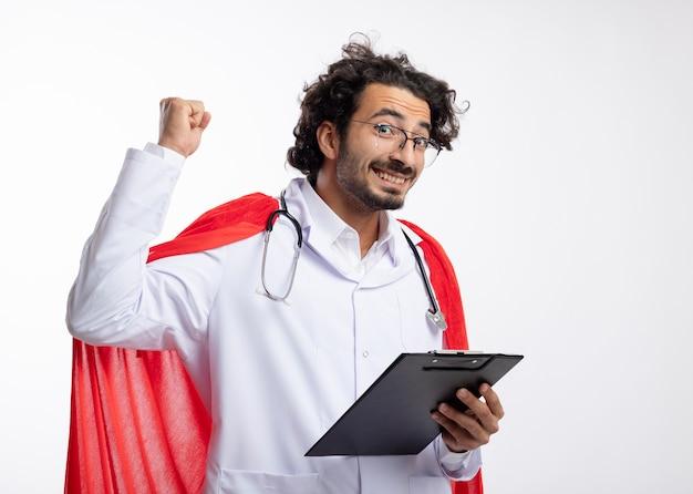 Glimlachende jonge blanke man in optische bril dragen arts uniform met rode mantel en met stethoscoop om nek staat met opgeheven vuist omhoog en houdt klembord op witte muur
