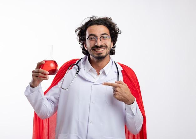 Glimlachende jonge blanke man in optische bril dragen arts uniform met rode mantel en stethoscoop om nek houdt en wijst op rode chemische vloeistof in glazen kolf