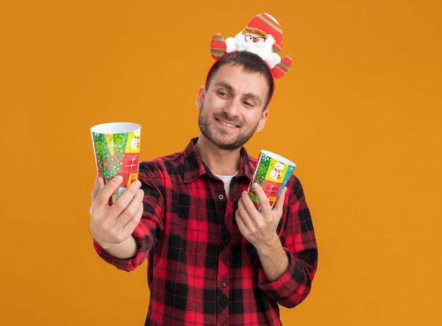 Glimlachende jonge blanke man met de hoofdband van de kerstman met plastic kerstbekers die zich uitstrekken een kijken ernaar geïsoleerd op een oranje achtergrond met kopie ruimte