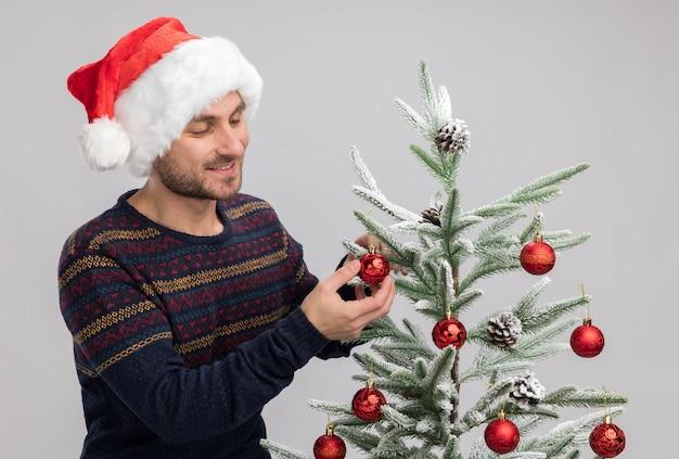 Glimlachende jonge blanke man met een kerstmuts die in de buurt van de kerstboom staat en ernaar kijkt en een kerstbal aanraakt die op een witte muur is geïsoleerd