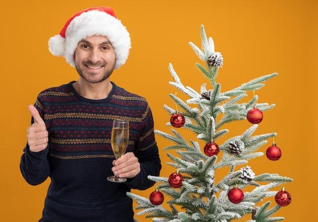 Glimlachende jonge blanke man met een kerstmuts die in de buurt van een versierde kerstboom staat en een glas champagne vasthoudt en duim omhoog laat zien geïsoleerd op een oranje muur
